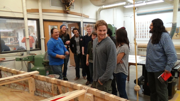 Art class visits the woodshop to see the project