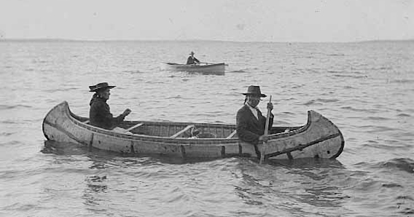 Two people paddling a birchbark canoe in 1910. Another pleasure boat is visible in background