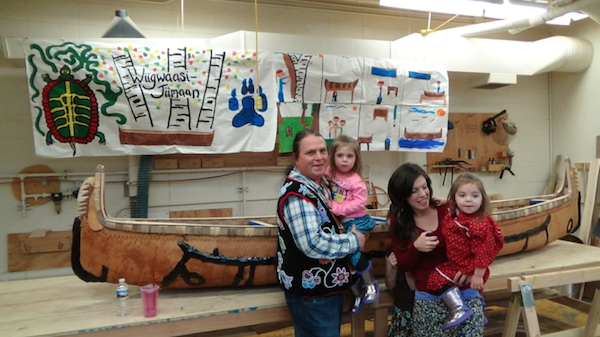 Wayne and his family in front of finished canoe