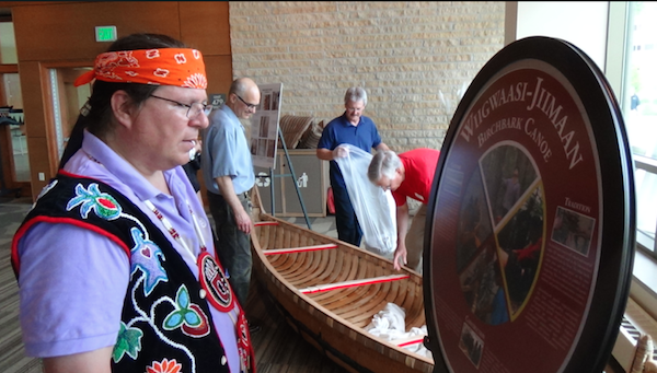 Wayne inspects sign created to commemorate canoe project at Dejope Hall