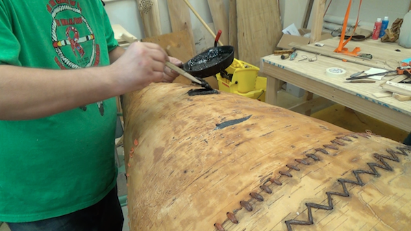 applying pitch with a stick to the bottom of the canoe