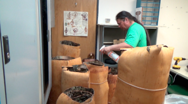Wayne spraying rolls of birchbark to keep them moist