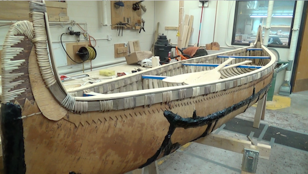 The completed canoe in wood shop, with finished paddles