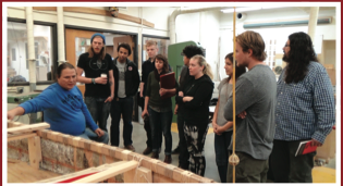 scene of Wayne speaking to class in woodshop