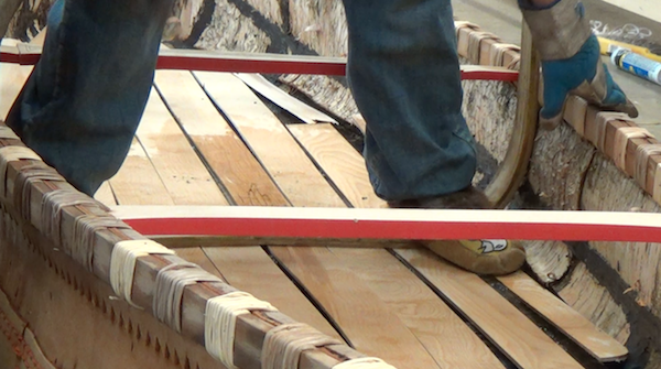 Wayne uses his feet, fitted with mocassins to finish the bending in the canoe.  The rib is bent into the proper shape while others hold sides of canoe
