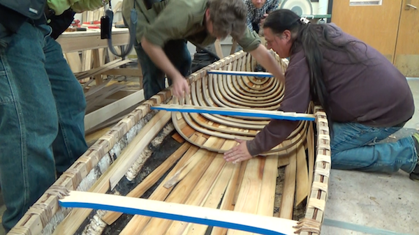 sheathing being added at middle of canoe, underneath ribs